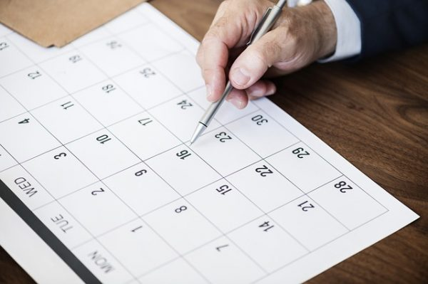 A hand holding a pen points to a date on the calendar chosen for office relocation
