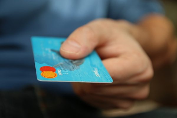 A man's hand holding a credit card, paying for packing services