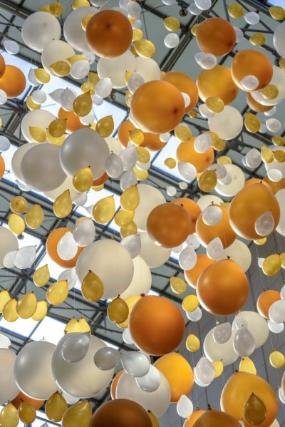 Many balloons – yellow, white, and golden