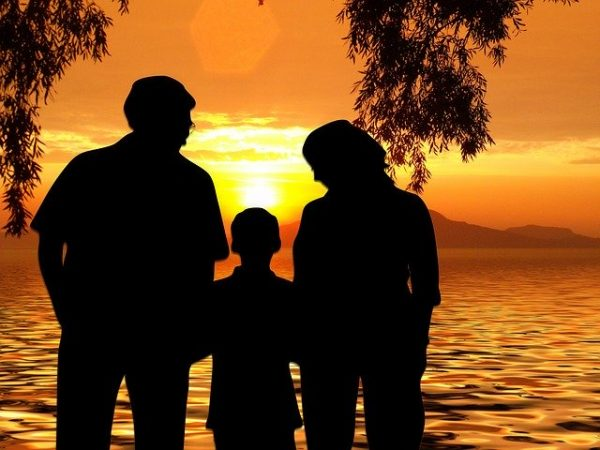 Parents and a child watching a sunset together