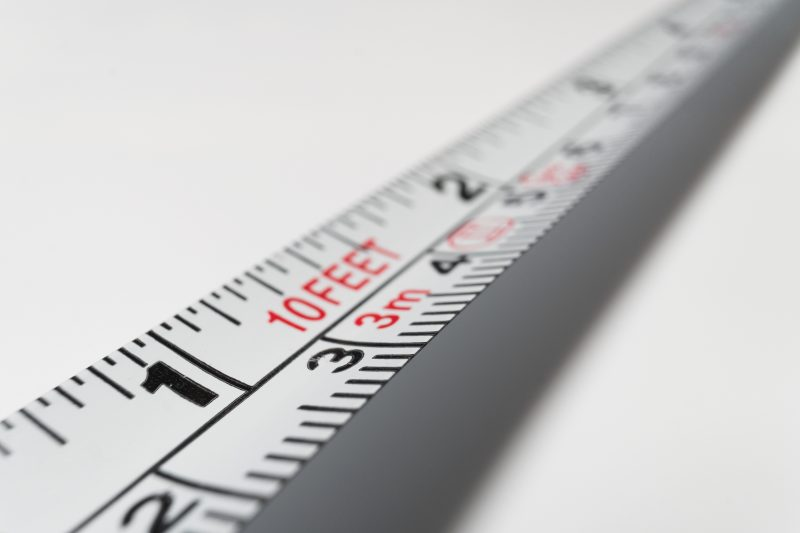 A white 10-foot steel measuring tape
