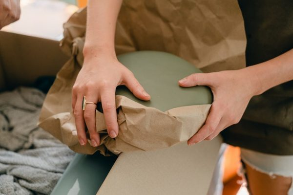 Person putting a dish in wrapping paper.