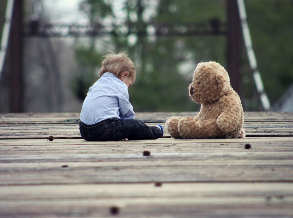 A kid playing with a teddy bear